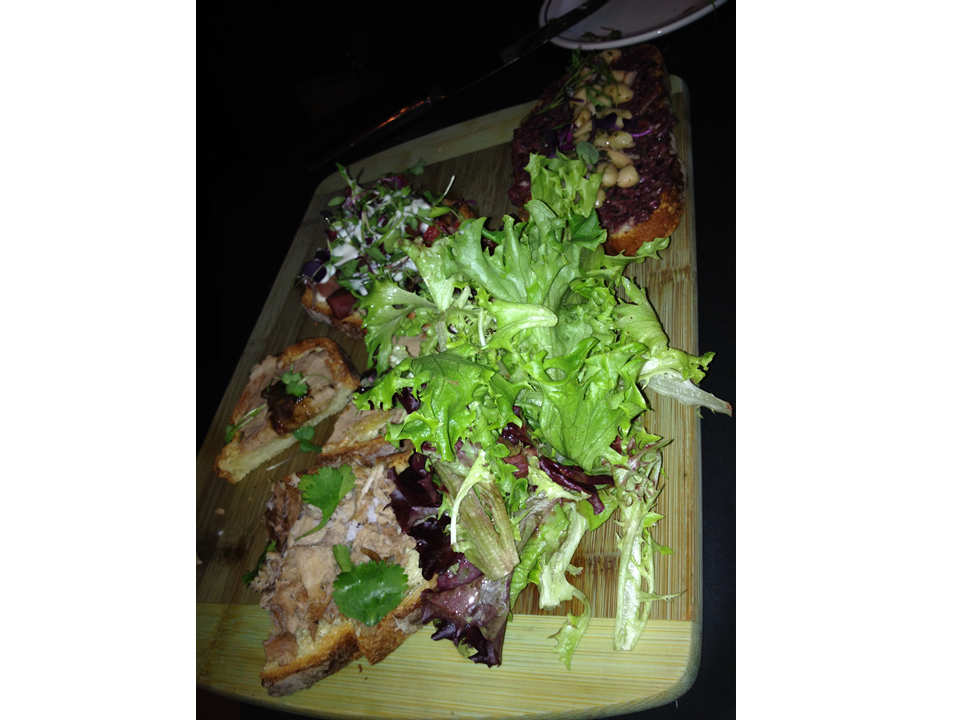 Figure 1.  A bruschetta board after we dug into it.  You can still see the remnants of the white bean, kalamata olive tapenade; lardon bacon, micro greens, tomato, house truffle aioli; and roast pork, lime, sea salt, and cilantro bruschettas.